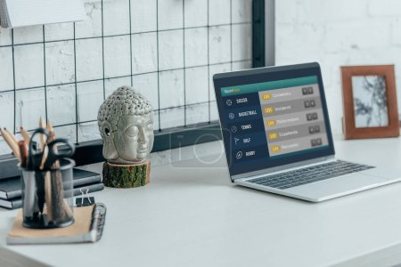Laptop with loaded sportbets page on table in modern office
