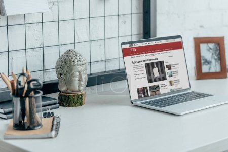 Photo for Laptop with loaded bbc news page on table in modern office - Royalty Free Image