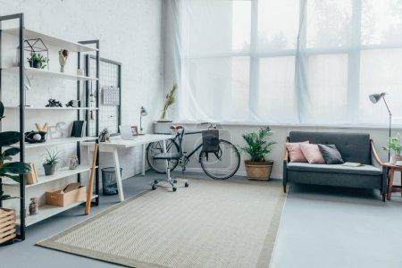 Photo pour Intérieur de la salle de séjour avec vélos, table, étagères et canapé - image libre de droit