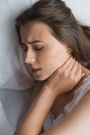 Photo pour Vue de dessus de la jeune femme souffrant de douleur au cou alors qu'elle était couchée au lit - image libre de droit