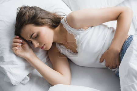 high angle view of young woman suffering from stomach ache in bed