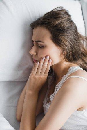 Photo pour Vue de dessus de la jeune femme souffrant de douleur dentaire alors qu'elle était couchée au lit - image libre de droit