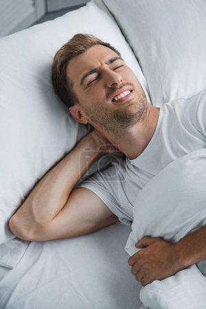 young man lying in bed and suffering from pain in neck
