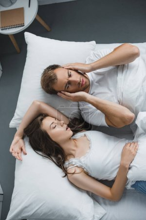 top view of man closing ears and looking at snoring woman in bed