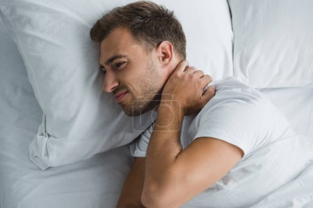 top view of young man lying in bed and suffering from pain in neck