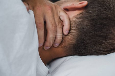 close-up view of man suffering from pain in neck while lying on bed