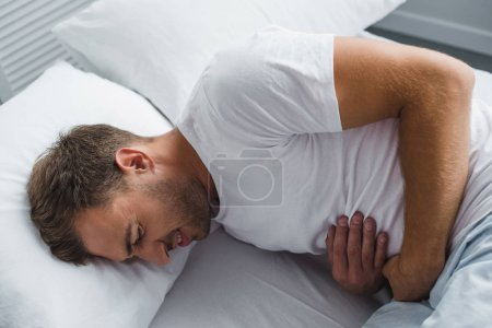 high angle view of man lying in bed and suffering from stomach pain