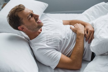 high angle view of man lying in bed and suffering from stomach ache