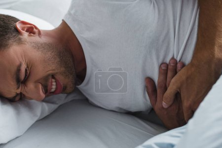 cropped shot of man suffering from abdominal pain on bed