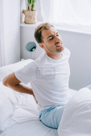 young man in pajamas sitting on bed and suffering from back pain