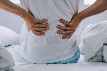 Photo pour Recadrée tir d'homme assis sur le lit et souffrant de maux de dos - image libre de droit