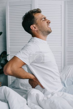 side view of young man in pajamas suffering from back pain while sitting on bed