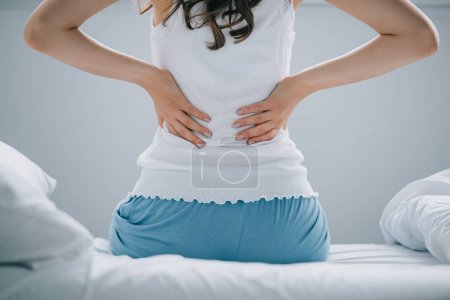 back view of young woman in pajamas suffering from back pain on bed