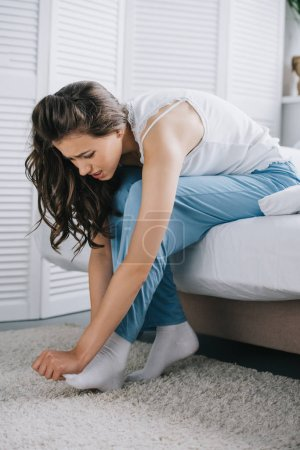 young woman suffering from foot pain while sitting on bed