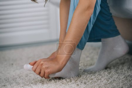 cropped shot of woman having foot pain in bedroom