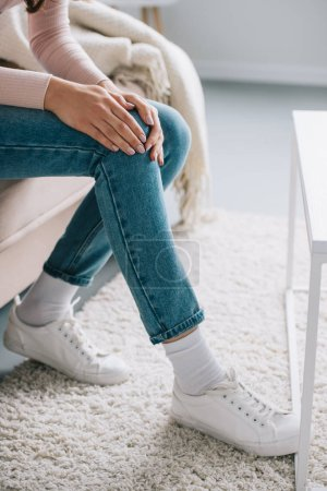 cropped shot of woman sitting on couch and suffering from pain in knee