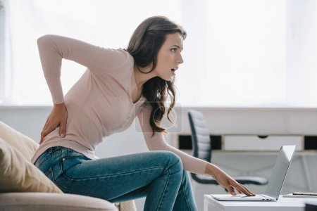 Photo for Side view of young woman suffering from back pain while using laptop at home - Royalty Free Image