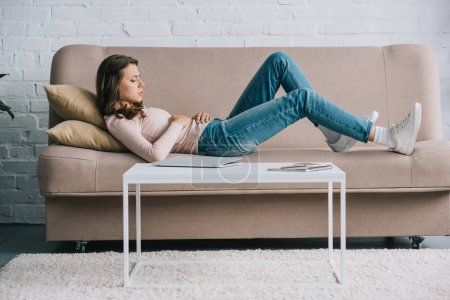 side view of young woman with abdominal pain lying on couch at home