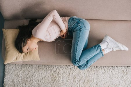 top view of young woman suffering from stomach ache while lying on sofa at home