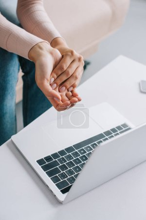 cropped shot of woman suffering from pain in hand while using laptop