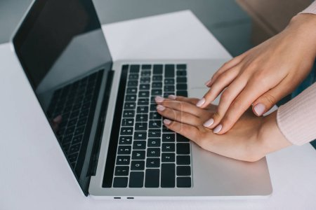 close-up partial view of woman rubbing hand while using laptop with blank screen