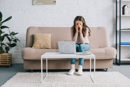 young woman with headache rubbing nose bridge while working with laptop at home