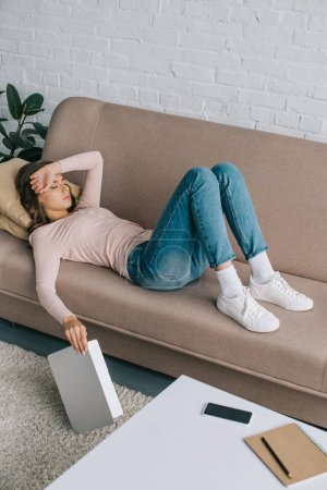 high angle view of young woman with headache lying on sofa and holding laptop
