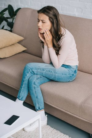 high angle view of young woman suffering from tooth pain while sitting on couch at home