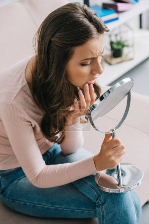 high angle view of young woman with tooth pain sitting and looking at mirror