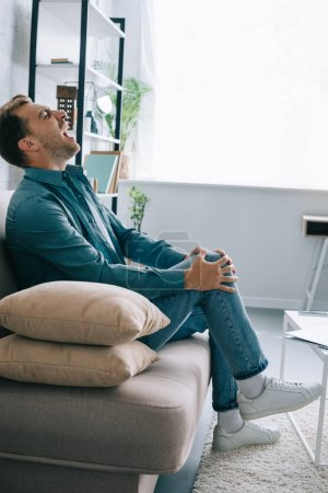 side view of man sitting on couch and suffering from knee pain at home