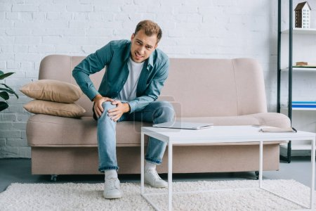 young man suffering from knee pain and looking at camera while sitting on couch