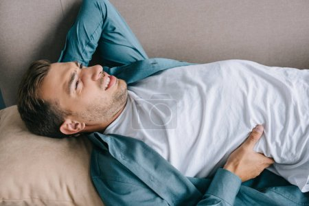 young man suffering from back pain and lying on couch