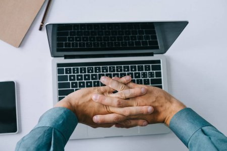 Photo for Partial top view of man stretching hands while using laptop - Royalty Free Image