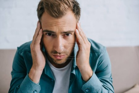 young man with headache looking at camera while sitting at home