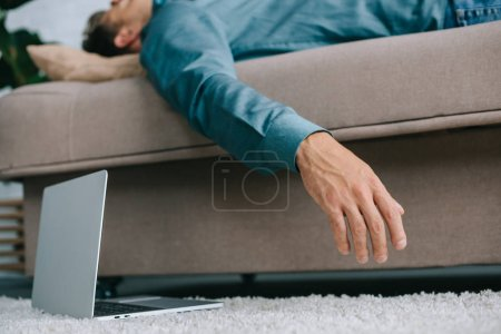close-up view of laptop on carpet and sick man lying on sofa