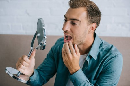young man with toothache looking at mirror while sitting at home