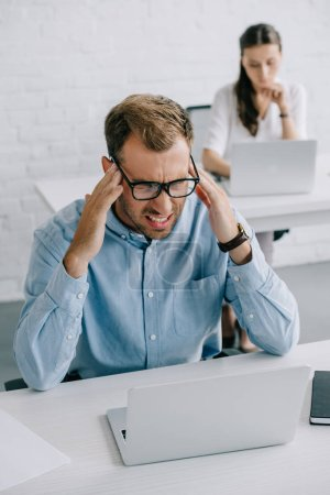 high angle view of businessman in eyeglasses suffering from headache while working with laptop in office