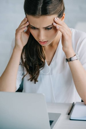 young businesswoman suffering from headache while working with laptop
