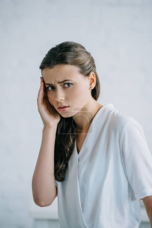 young businesswoman suffering from headache and looking at camera