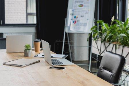 Photo pour Ordinateurs portables, smartphone et café pour aller sur une table en bois dans le bureau - image libre de droit