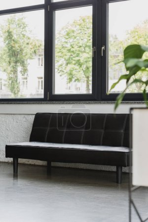 empty modern black couch near window in modern office