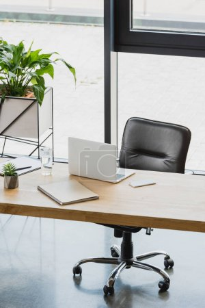 Photo for Laptop and smartphone on wooden table in modern office - Royalty Free Image