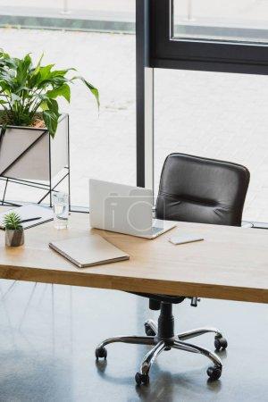 Photo pour Ordinateur portable et smartphone sur une table en bois dans le bureau moderne - image libre de droit
