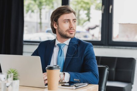 handsome young businessman using laptop and looking away in office