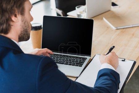 abgeschnittene Aufnahme eines Geschäftsmannes, der Notizen auf Klemmbrett macht und Laptop mit leerem Bildschirm am Arbeitsplatz benutzt