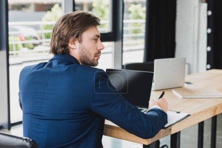 Foto de Vista posterior de joven empresario busca a escribir en el portapapeles y usando laptop en la oficina - Imagen libre de derechos