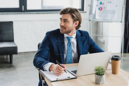 Photo for Smiling young businessman looking away while writing on clipboard and using laptop in office - Royalty Free Image