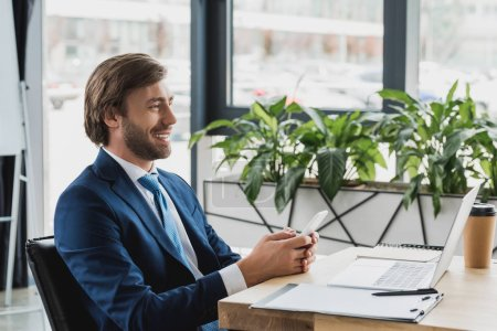 side view of smiling young businessman using smartphone and laptop in office