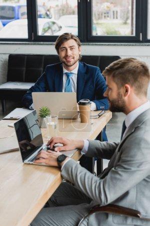 jeunes hommes d'affaires en costume à l'aide d'ordinateurs portables et de travailler ensemble au bureau