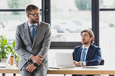 young businessman using laptop and looking at colleague sitting on table in office